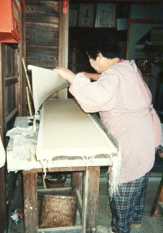 Mrs. Fukunishi carefully lifts a sheet of this fragile paper