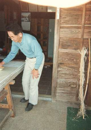 Mr Fukunishi brushes the paper onto the drying board